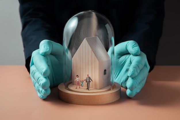 コロナウイルスコンセプト中の安全衛生保険。ガラスのドームの家の中を歩いている家族のミニチュアフィギュア