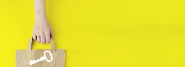 안전 및 보안 쇼핑 개념입니다. 노란색 배경에 홀로그램 키 키워드 아이콘이 있는 재활용된 갈색 종이 쇼핑백이 평평하게 놓여 있습니다. 여름 판매 개념입니다. 배달 서비스 개념입니다.