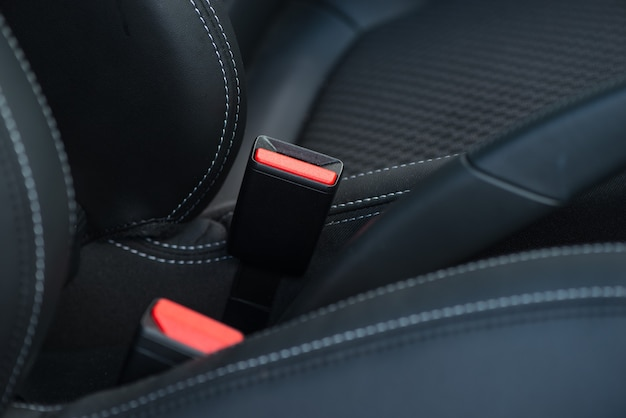 Safety belt on a black leather chair. closeup