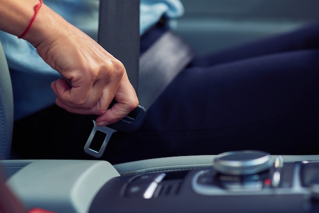 安全性。車のハンドルの後ろに座ってシートベルトを締めている女性のクロップドショット、人と交通機関、車両のコンセプト