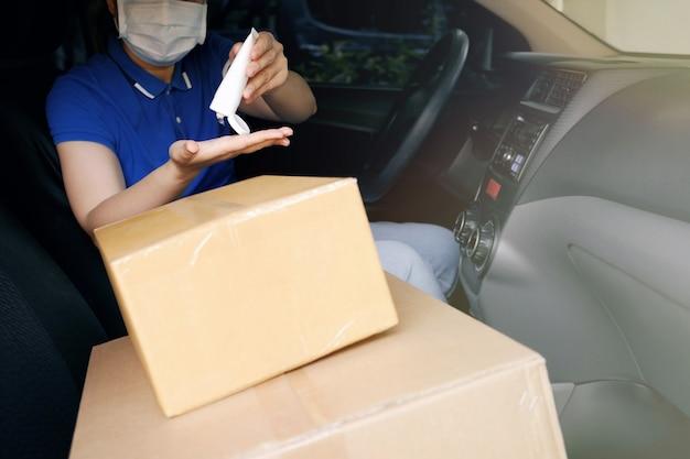 코로나 바이러스 (covid-19) 유행성, 택배 운전자가 의료용 보호 마스크를 착용 한 상태에서 안전 배달 서비스 택배, 밴의 골판지 상자 위에 알코올 젤 손 소독제를 손에 바르십시오.