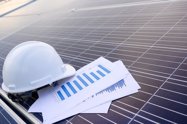 Safety engineer helmet in industrial premises where solar panels are installed using solar energy first concept solar power station background.