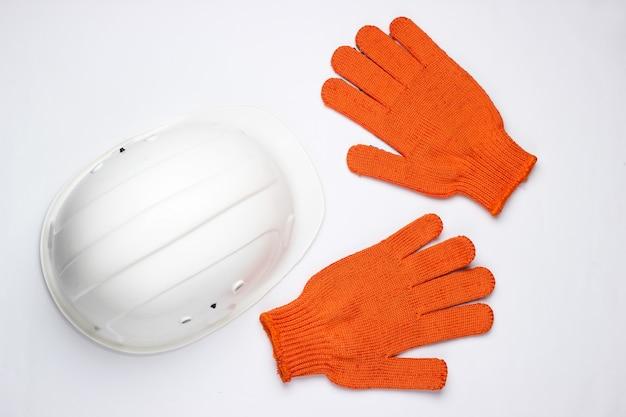 安全装置。建設用ヘルメット、白い背景の上の手袋。上面図