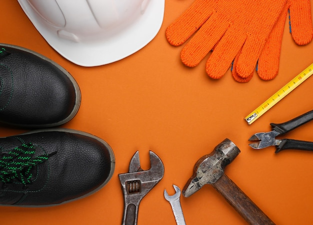 Safety equipment and work tool on brown background. top view. cop space