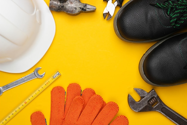 Safety equipment and work tool on a yellow background. top view. copy space