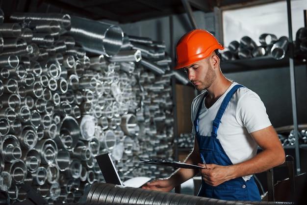 Безопасность прежде всего. в каске. мужчина в военной форме работает на производстве. современные промышленные технологии.