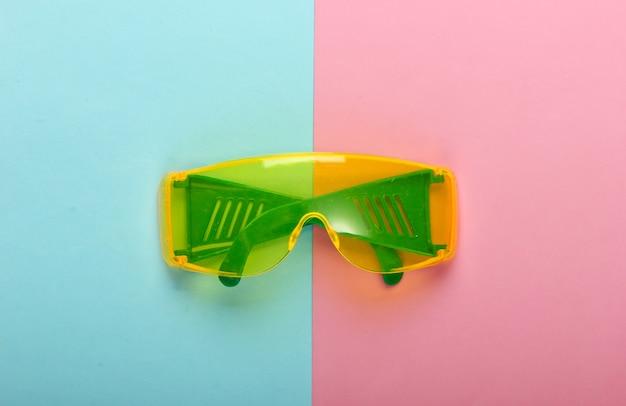 青ピンクのパステルカラーの背景に安全メガネ。上面図