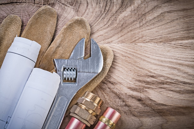 Safety gloves copper water pipe blueprints hose nipples adjustable spanner on wooden board plumbing concept