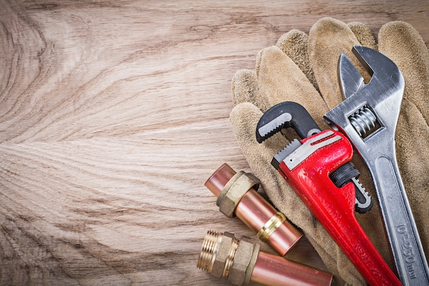Safety gloves copper water pipe wrench hose nipples adjustable spanner on wooden board plumbing concept