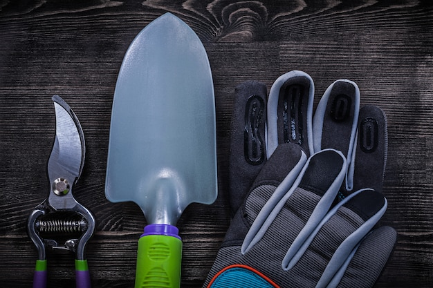 Safety gloves sharp secateurs hand spade on wooden board