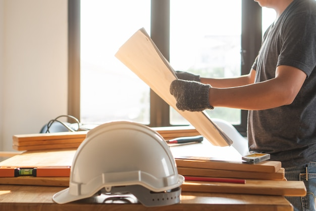 Safety hard hat on the table and worker as background.