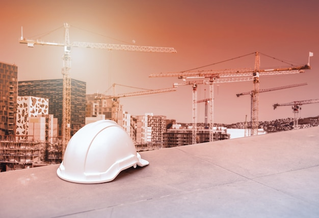 Safety hard helmet for construction engineer and worker on cranes and building blurred background