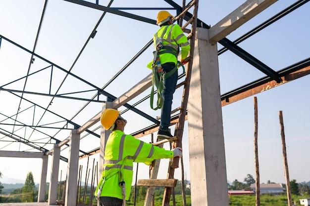 건설 현장의 안전 높이 장비; 아시아 노동자는 지붕을 설치하기 위해 안전 높이 장비를 착용합니다. 안전 바디 하네스 용 후크가있는 작업자 용 추락 방지 장치.