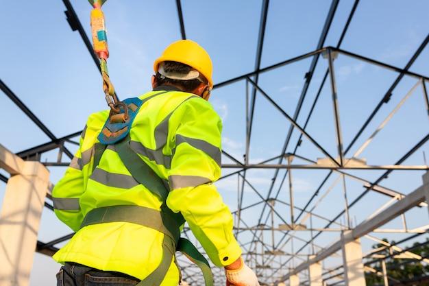 건설 현장의 안전 높이 장비; 아시아 노동자는 지붕을 설치하기 위해 안전 높이 장비를 착용합니다. 안전 바디 하네스 용 후크가있는 작업자 용 추락 방지 장치. 프리미엄 사진