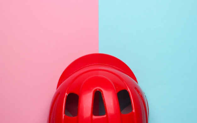 Safety helmet for active sports on a pink-blue background. top view