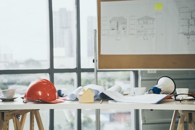 건설 프로젝트 현장에서 작업 테이블에 안전 헬멧 및 목조 주택