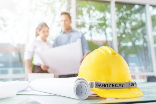 Safety helmet and blueprint on working table with businessman and woman in background