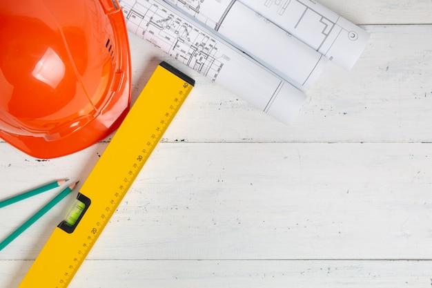 Защитный шлем, уровень конструкции, карандаши и технические чертежи с копией пространства