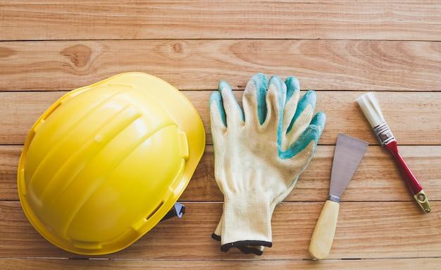Защитный шлем, перчатки, шпатель и кисточка на деревянной доске сверху