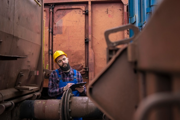 Safety inspector checking train or connection joints between railroad cars and wagons.
