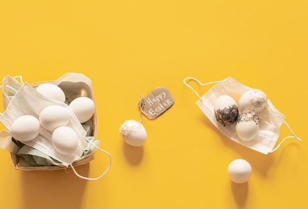 Maschere di sicurezza e uova distese. buona pasqua durante la pandemia di coronavirus.