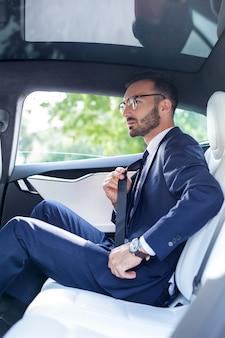 Безопасность имеет значение. молодой элегантный мужчина в костюме пристегивает ремень безопасности, сидя на заднем сиденье