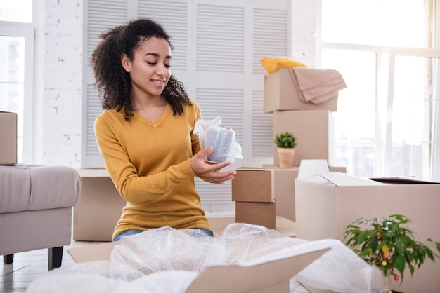 Safety measures. beautiful curly-haired girl wrapping a tea cup securely before putting it into a box and smiling charmingly