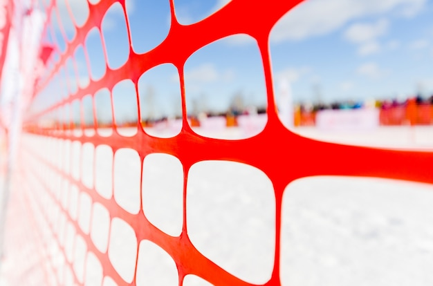 Safety outdoor slope track fence, winter background. fence to protect spectators at sports events, or to indicate course at extreme sports - dog sledding, snowboarding or skiing