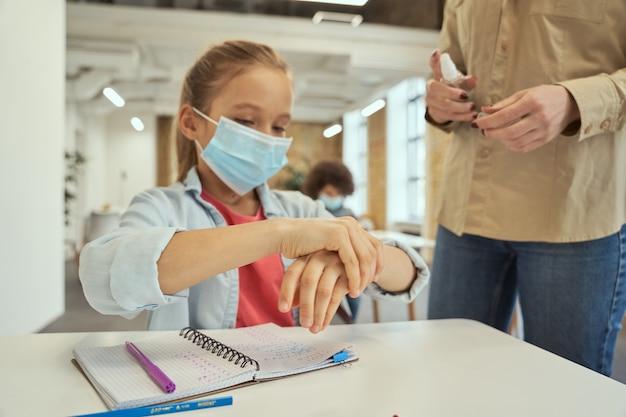 안전 규칙은 보호 마스크 여교사를 쓴 어린 여학생의 깨끗한 손을 닫습니다
