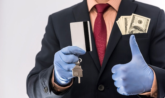 Safety sale or rent house man in medical gloves hold house key and dollar