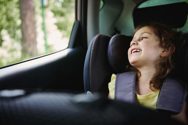 ブースターチャイルドシートに子供を固定した車での安全旅行。子車saetの愛らしい女の子