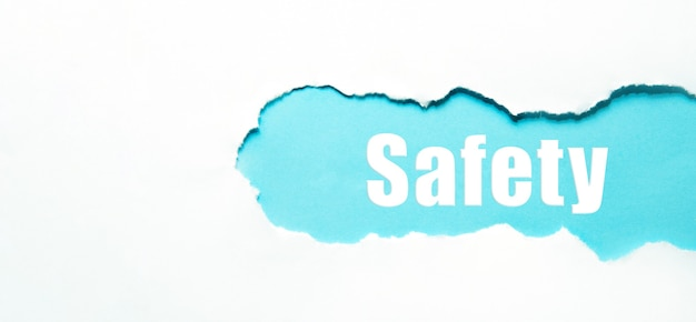 Safety word under torn white paper on blue.