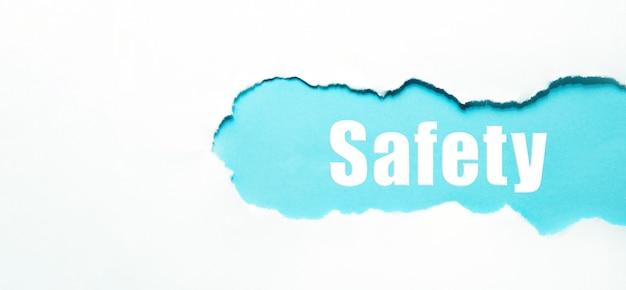 Слово безопасности под порванной белой бумагой на синем.