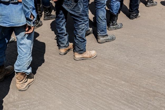安全作業ブーツと労働者の汚れのジーンズ。