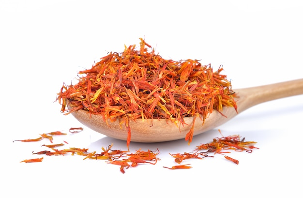 Safflower petals in a spoon isolated