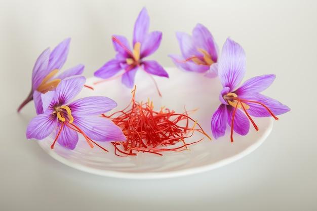 白いプレートにサフランの花とサフランの糸。最も高価なスパイス。