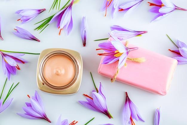 Цветы шафрана, косметический крем и шафрановое мыло на белом фоне. крем с экстрактом шафрана.