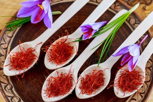 나무 숟가락에 사프란입니다. 세라믹 접시에 나무 숟가락에 말린 사프란 향신료. 음식과 전통 약초에 사용되는 사프란 향신료
