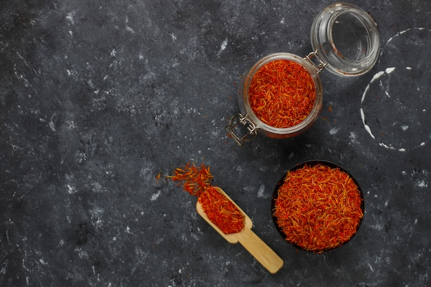 Saffron spice herb in wooden spoon, black background
