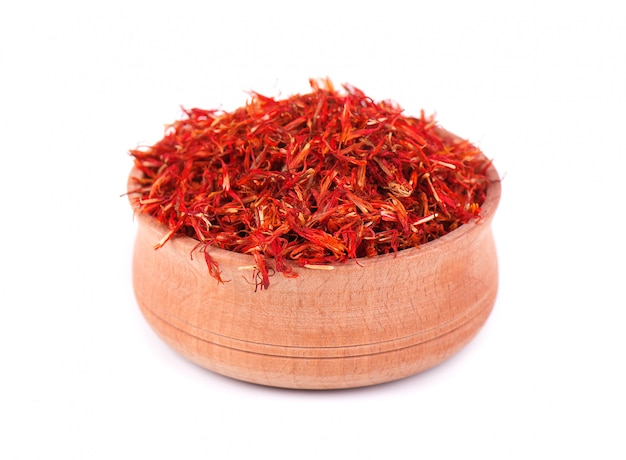 Saffron spice in wooden bowl isolated on white background