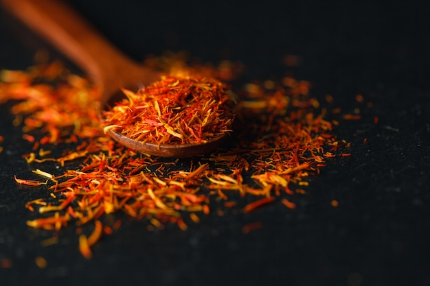 Saffron in a spoon on a dark table, selective focus, macro shot, shallow depth of field