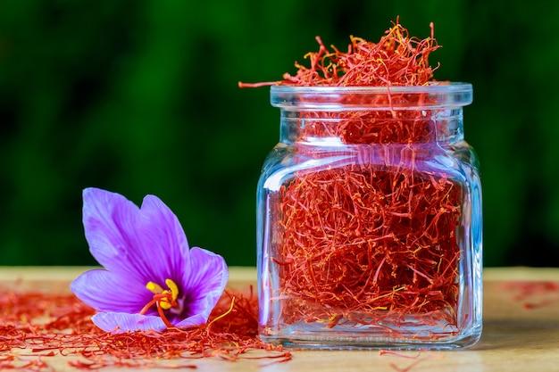 Рыльца шафрана разбросаны по деревянной поверхности из стеклянной бутылки
