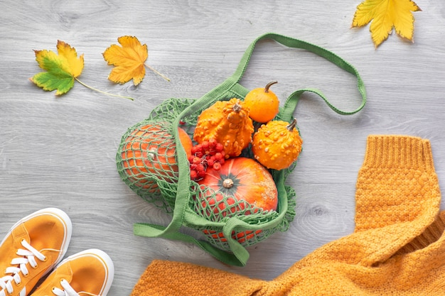 Safran yellow and orange pumpkins in mesh bag with yellow sweater sleave. creative autumntime background. autumn flat lay on light wood.