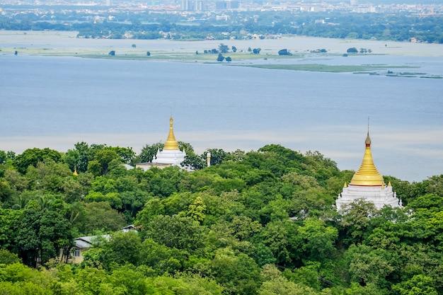 Вид с воздуха города мандалая с храмами, золотой пагодой, рекой иравади и мостами от холма sagaing. достопримечательность и популярные для туристов достопримечательности в мьянме