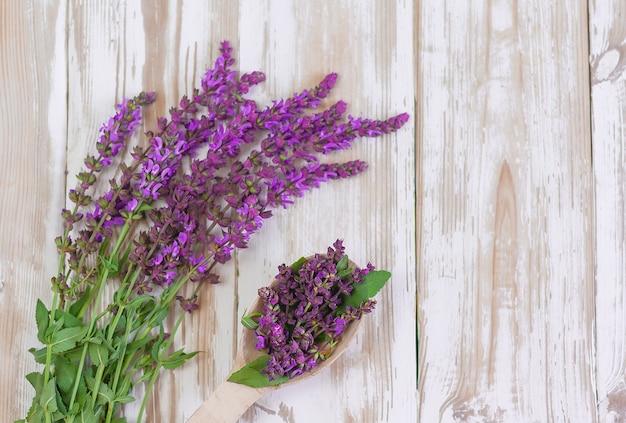 コピースペースと白い木製の背景にセージの花。薬草、香辛料、アロマテラピー、ホメオパシー、天然化粧品。