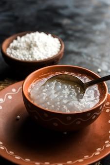 아기와 유아를 위한 사고 또는 사부다나 죽 요리법, 숟가락과 선택적인 초점이 있는 그릇에 제공