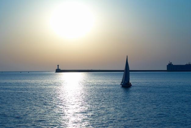 海の夕日に対する帆船。青い海の風景。