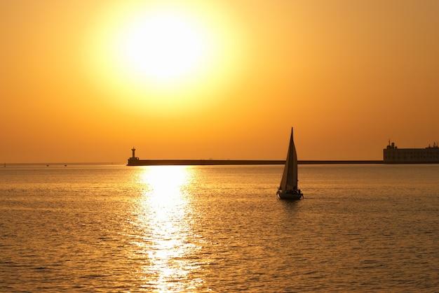 海の夕日に対する帆船。カラフルな海の風景。