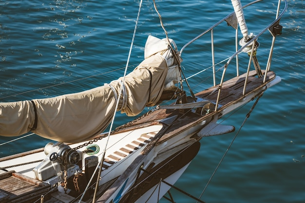 Sail folded over the prow deck of an old wooden sailboat