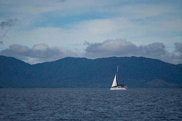 Парусник в море в вечернем солнечном свете на фоне красивых больших гор, активных приключений ...